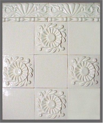 handmade wall demonstration of ceramic tiles with high relief floral designs and trim tiles, all with a  one color glaze