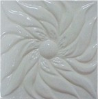 handmade ceramic tile with a high relief flower design and a one color glaze